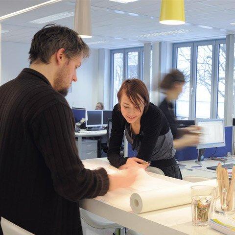 Auszubildende lehnt an einem Tisch im Büro und schaut mit einem Mitarbeiter auf Dokumente